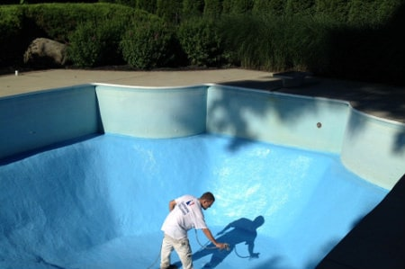 workers apply new commercial coating to inground pool