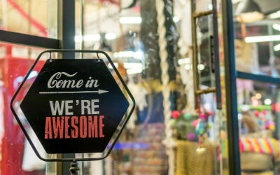"A sign on a store front that reads ""Come in, We're awesome"""