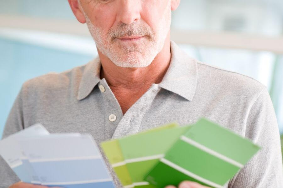 Man looking at different paint swatches