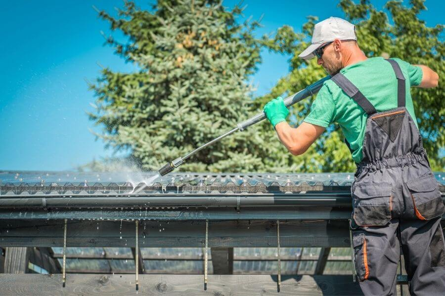 man power washing a business roof